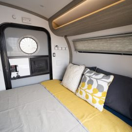 View of bed space and overhead cubby.